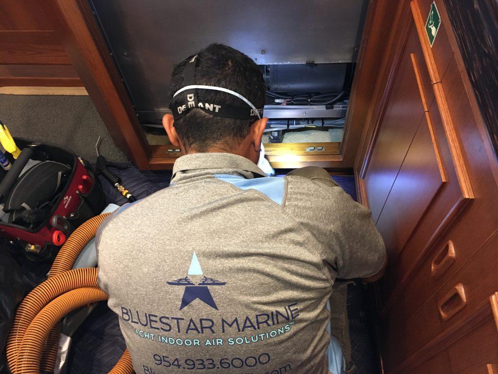 Bluestar Marine technician cleaning an air handling unit in a yacht